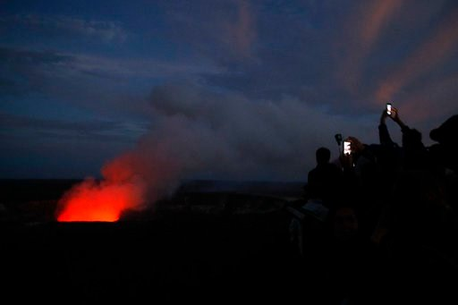 (AP Photo/Jae C. Hong). Visitors take pictures as Kilauea's summit crater glows red in Volcanoes National Park, Hawaii, Wednesday, May 9, 2018. Geologists warned Wednesday that Hawaii's Kilauea volcano could erupt explosively and send boulders, rocks a...