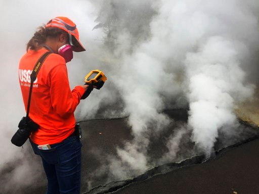 (U.S. Geological Survey via AP). This photo provided by the U.S. Geological Survey shows a Hawaii Volcano Observatory geologist recording a temperature of 103 degrees C (218 degrees F) at a crack along Nohea Street in Leilani Estates near the town of P...