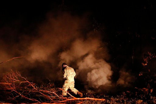 (AP Photo/Jae C. Hong). Sgt. 1st Class Carl Satterwaite, of the U.S. National Guard, tests air quality near cracks emitting volcanic gases from a lava flow in the Leilani Estates subdivision near Pahoa, Hawaii Thursday, May 10, 2018. Kilauea has destro...