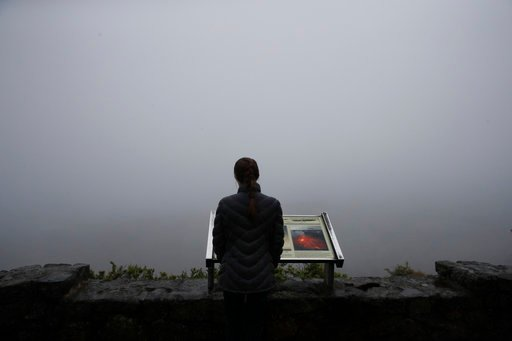 (AP Photo/Jae C. Hong). A visitor stands outside the Jaggar Museum overlooking Kilauea's summit crater in Volcanoes National Park, Hawaii, Thursday, May 10, 2018. The park is closing Friday due to the threat of an explosive volcanic eruption.