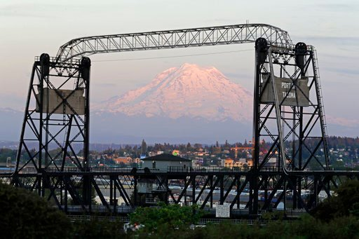 (AP Photo/Ted S. Warren). In this May 7, 2018 photo, Mount Rainier is seen at dusk and framed by the Murray Morgan Bridge in downtown Tacoma, Wash. The eruption of the Kilauea volcano in Hawaii has geologic experts along the West Coast warily eyeing th...