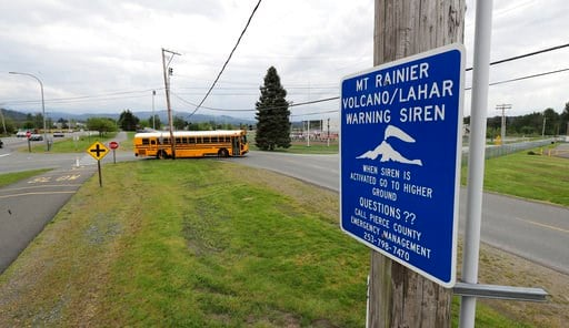 (AP Photo/Ted S. Warren). In this May 8, 2018 photo, a sign under a lahar warning siren is shown as a school bus drives near Orting Middle School in Orting, Wash. The siren would sound if nearby Mount Rainier erupts or triggers a lahar mud flow, which ...