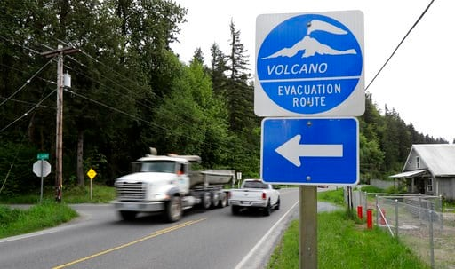 (AP Photo/Ted S. Warren). In this May 8, 2018 photo, a volcano evacuation route sign directs traffic and pedestrians to an area of higher ground near Orting, Wash. should nearby Mount Rainier erupt or trigger a lahar mud flow. The eruption of the Kilau...