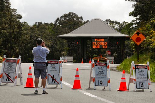 (AP Photo/Jae C. Hong). Ken Gadd, a first-time visitor from Dayton, Ohio, takes pictures of the entrance to Volcanoes National Park, Hawaii, Friday, May 11, 2018. The park is closed due to the threat of an explosive volcanic eruption. Warnings that Haw...