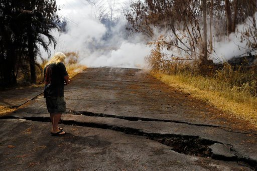 (AP Photo/Jae C. Hong). Steve Clapper, a resident living in the Leilani Estates subdivision, takes pictures of cracks on the street as gases continue to rise from fissures Friday, May 11, 2018, near Pahoa, Hawaii. Kilauea has destroyed more than 35 str...