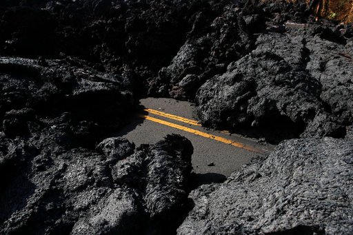 (AP Photo/Jae C. Hong). Center lane lines are partially visible along the lava-covered road in the Leilani Estates subdivision near Pahoa, Hawaii, Friday, May 11, 2018. Kilauea has destroyed more than 35 structures since it began releasing lava from ve...