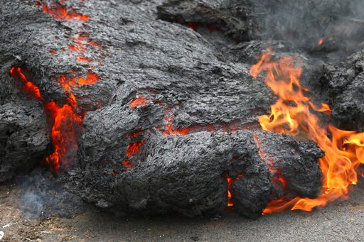 (AP Photo/Caleb Jones, File). File - In this May 5, 2018, file photo, lava burns across a road in the Leilani Estates subdivision near Pahoa, Hawaii. The lava hisses, crackles and pops. It roars like an engine as it sloshes and bubbles. It shoots into ...