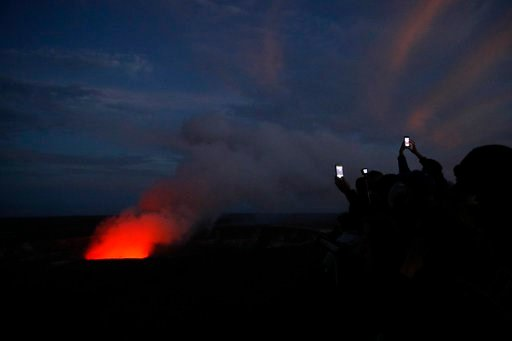 (AP Photo/Jae C. Hong, File). File - In this May 9, 2018, file photo, visitors take pictures as Kilauea's summit crater glows red in Volcanoes National Park, Hawaii. The lava hisses, crackles and pops. It roars like an engine as it sloshes and bubbles....