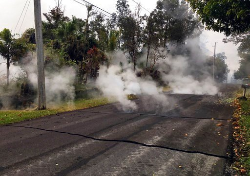 (U.S. Geological Survey via AP, File). File - This May 7, 2018, file photo from the U.S. Geological Survey shows gas and steam rising from multiple fissures on Moku Street in the Leilani Estates Subdivision near Pahoa on the island of Hawaii. The lava ...
