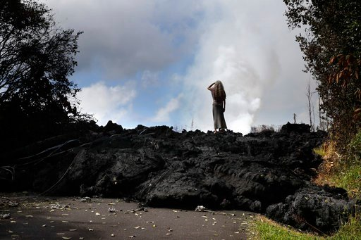 (AP Photo/Jae C. Hong, File). File - In this May 11, 2018 file photo, Hannique Ruder, a 65-year-old resident living in the Leilani Estates subdivision, stands on the mound of hardened lava near Pahoa, Hawaii. The lava hisses, crackles and pops. It roar...
