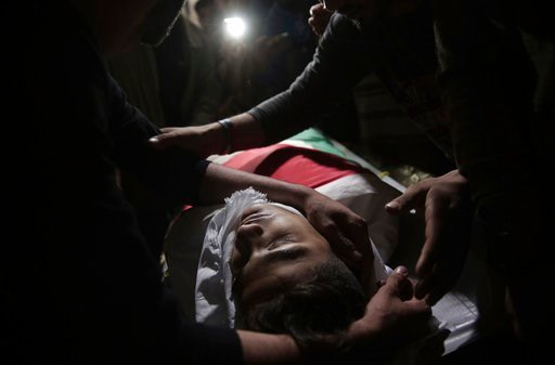 (AP Photo/Khalil Hamra). Relatives of 15-year-old Palestinian Jamal Afaneh mourn over his body at the family house during his funeral in Rafah refugee camp, southern Gaza Strip, Sunday, May 13, 2018.
