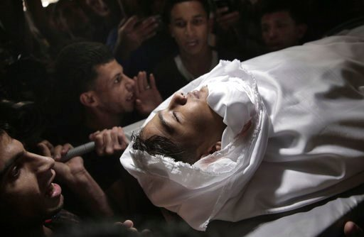(AP Photo/Khalil Hamra). Mourners chant angry slogans as they carry the body of 15-year-old Palestinian Jamal Afaneh during his funeral in Rafah refugee camp, southern Gaza Strip, Sunday, May 13, 2018.