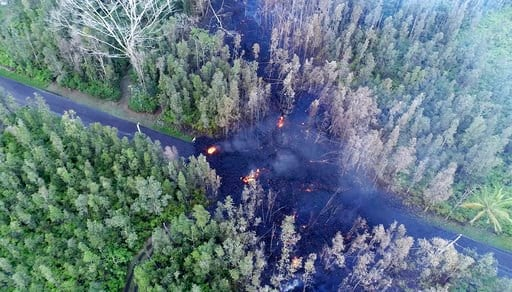 (Byron Matthews via AP, File). File - In this May 4, 2018, file frame from video, lava flows over a road in the Puna District as a result of the eruption from Kilauea Volcano on Hawaii's Big Island. The lava hisses, crackles and pops. It roars like an ...