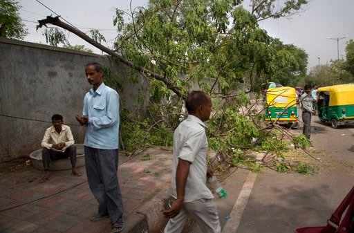 (AP Photo/Manish Swarup). Commuters walk past an uprooted tree from yesterday's sudden storm in New Delhi, India, Monday, May 14, 2018. Powerful wind and rain storms have swept across northern India, with authorities saying dozens of people have been k...