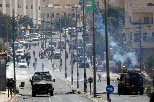 (AP Photo/Majdi Mohammed). Palestinians clash with Israeli troops following a protest against the opening of the U.S. embassy in Jerusalem, in the West Bank city of Bethlehem, Monday, May 13, 2018.