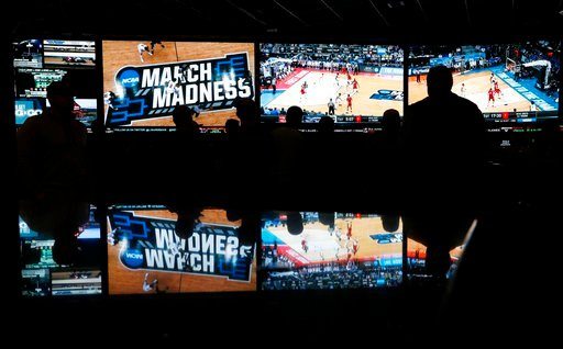 (AP Photo/John Locher). In this March 15, 2018 photo, people watch coverage of the first round of the NCAA college basketball tournament at the Westgate Superbook sports book in Las Vegas. The Supreme Court has struck down a federal law that bars gambl...