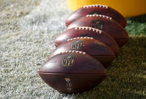 (AP Photo/Don Wright, File). FILE - In this Jan. 14, 2018 file photo, NFL footballs sit on the field during warm ups before an NFL divisional football AFC playoff game between the Pittsburgh Steelers and the Jacksonville Jaguars in Pittsburgh. The NFL ...