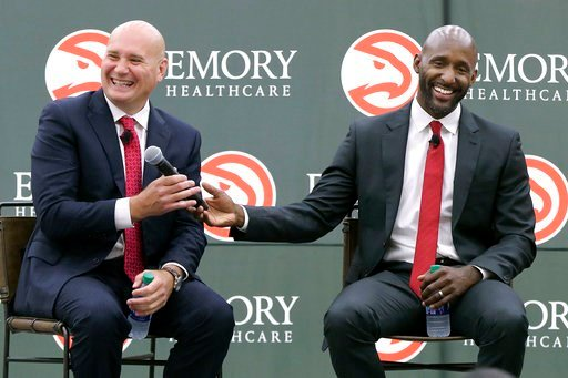 (Curtis Compton/Atlanta Journal-Constitution via AP). Atlanta Hawks general manager Travis Schlenk, left, and Lloyd Pierce share a laugh during a press conference introducing Pierce as a full-time coach for the team on Monday, May 14, 2018, in Atlanta....