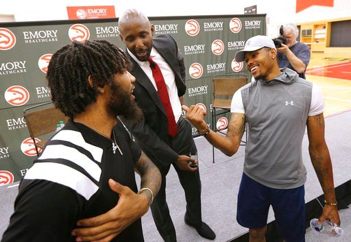 (Curtis Compton/Atlanta Journal-Constitution via AP). Atlanta Hawks players DeAndre' Bembry, left,  and Kent Bazemore welcome their new head coach Lloyd Pierce, center,  after a press conference on Monday, May 14, 2018, in Atlanta.