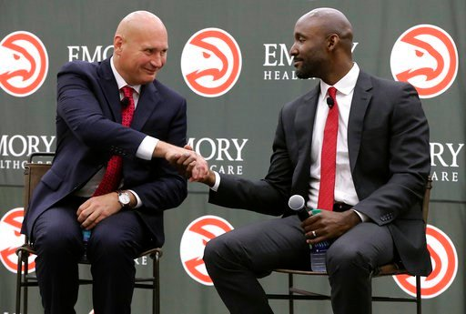 (Curtis Compton/Atlanta Journal-Constitution via AP). The Atlanta Hawks' general manager Travis Schlenk, left, shakes hands with Lloyd Pierce after introducing him as the team's full-time coach Monday, May 14, 2018, in Atlanta. Pierce joins the Hawks a...
