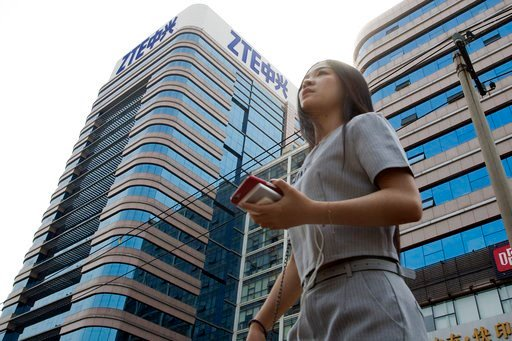 (AP Photo/Ng Han Guan). In this May 8, 2018, photo, a woman pass by a ZTE building in Beijing, China. President Donald Trump's weekend social media musings about China injected new uncertainty into the Washington's punishment of Chinese tech giant ZTE ...