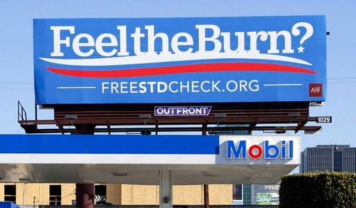 """(AP Photo/Nick Ut, File). FILE - This April 1, 2016 file photos shows a billboard above a gas station that reads """"Feel The Burn,"""" a play on then-presidential candidate Bernie Sanders' campaign slogan, """"Feel The Bern."""" It's actually promoting testing fo..."""