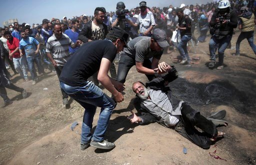 (AP Photo/Khalil Hamra). An elderly Palestinian man falls on the ground after being shot by Israeli troops during a deadly protest at the Gaza Strip's border with Israel, east of Khan Younis, Gaza Strip, Monday, May 14, 2018.