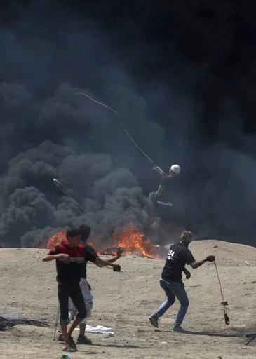 (AP Photo/Khalil Hamra). Palestinian protesters hurl stones at Israeli troops during a protest on the Gaza Strip's border with Israel, Monday, May 14, 2018.