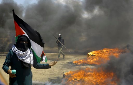 (AP Photo/Adel Hana). A woman holds a Palestinian flag as a protester burns tires near the Israeli border fence, east of Khan Younis, in the Gaza Strip, Monday, May 14, 2018.