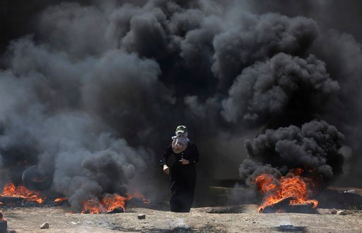 (AP Photo/Khalil Hamra). A Palestinian woman walks through black smoke from burning tires during a protest on the Gaza Strip's border with Israel, Monday, May 14, 2018.