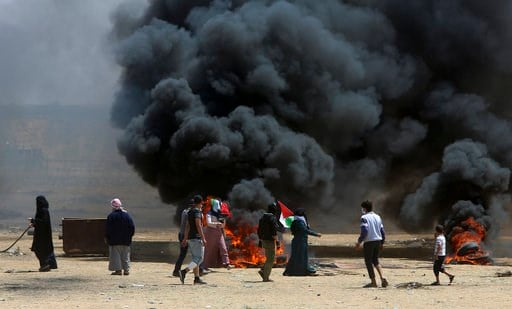(AP Photo/Adel Hana). Palestinian protesters burn tires near the Israeli border fence, east of Khan Younis, in the Gaza Strip, Monday, May 14, 2018.