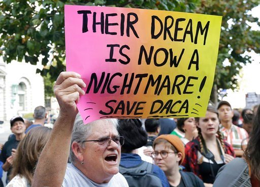 (AP Photo/Jeff Chiu, File). In this Sept. 15, 2017, file photo, Judy Weatherly, a supporter of the Deferred Action for Childhood Arrivals (DACA) holds up a sign during a protest outside of the Federal Building in San Francisco.