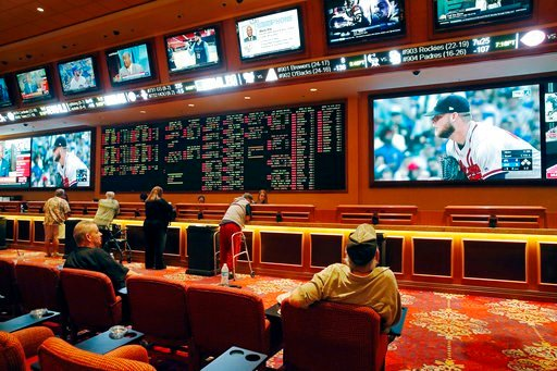 (AP Photo/John Locher). In this Monday, May 14, 2018 photo, people make bets in the sports book at the South Point hotel and casino in Las Vegas. Now that the U.S. Supreme Court has cleared the way for states to legalize sports betting, the race is on ...