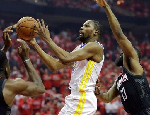 (AP Foto/David J. Phillip). El alero de los Warriors de Golden State, Kevin Durant, ataca el aro y deja atrás a James Harden, de los Rockets de Houston, en la primera mitad del juego 1 de la Final de la Conferencia Oeste el lunes 14 de mayo de 2018 en ...