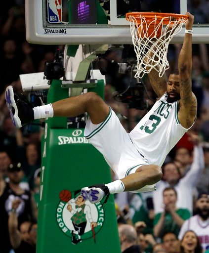(AP Photo/Charles Krupa). Boston Celtics forward Marcus Morris hangs from the rim after dunking against the Cleveland Cavaliers during the first half in Game 2 of the NBA basketball Eastern Conference finals Tuesday, May 15, 2018, in Boston.