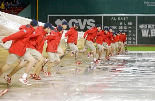 (AP Photo/Steven Senne). Fenway Park grounds crew workers remove a tarp from the field during a rain delay before a scheduled baseball game between the Oakland Athletics and the Boston Red Sox, Tuesday, May 15, 2018, in Boston.