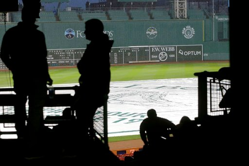 (AP Photo/Steven Senne). People wait in the stands during a rain delay at Fenway Park before a scheduled baseball game between the Oakland Athletics and the Boston Red Sox, Tuesday, May 15, 2018, in Boston.