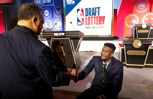 (AP Photo/Charles Rex Arbogast). Arizona's DeAndre Ayton, right, shakes hands with the Rev, Jesse Jackson before the NBA basketball draft lottery Tuesday, May 15, 2018, in Chicago.
