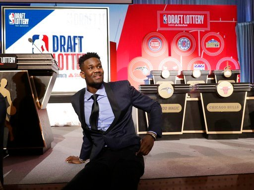 (AP Photo/Charles Rex Arbogast). DeAndre Ayton from Arizona sits on the stage before the NBA basketball draft lottery Tuesday, May 15, 2018, in Chicago.