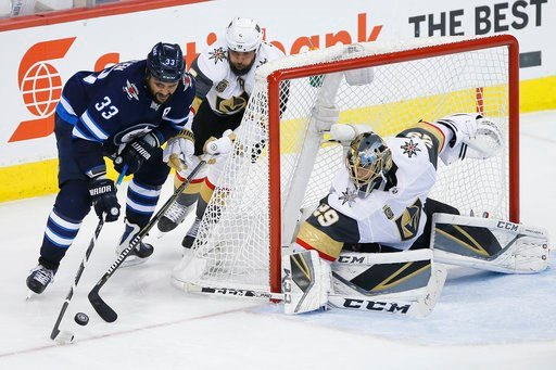 (John Woods/The Canadian Press via AP). Winnipeg Jets' Dustin Byfuglien (33) attempts the wraparound on Vegas Golden Knights' Deryk Engelland (5) and goaltender Marc-Andre Fleury (29) during the third period of Game 1 of the NHL hockey playoffs Western...