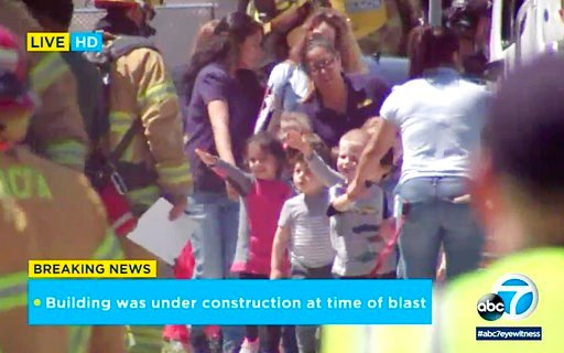 (KABC-TV via AP). In this photo taken from video provided by KABC-TV, children are evacuated from a preschool across the street from a building that was rocked by an explosion in Aliso Viejo, Calif., Tuesday afternoon, May 15, 2018.