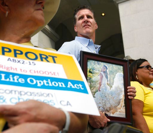 (AP Photo/Rich Pedroncelli, File). FILE - In this Sept. 24, 2015, file photo, Dan Diaz holds a photo of his late wife, Brittany Maynard, taken on their wedding day, during a rally calling for California Gov. Jerry Brown to sign right-to-die legislation...