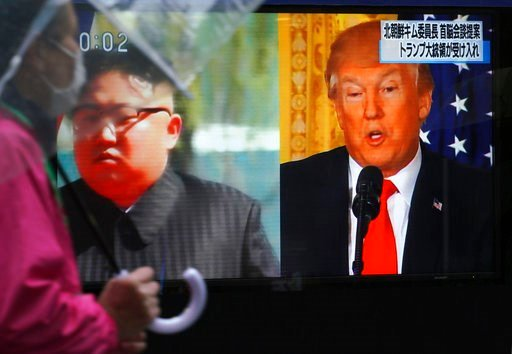 (AP Photo/Eugene Hoshiko). FILE - In this March 9, 2018, file photo, a man walks past a public TV screen showing North Korean leader Kim Jong Un, left, and U.S. President Donald Trump, right, in Tokyo. Pyongyang's threat to scrap the June 12 historic s...