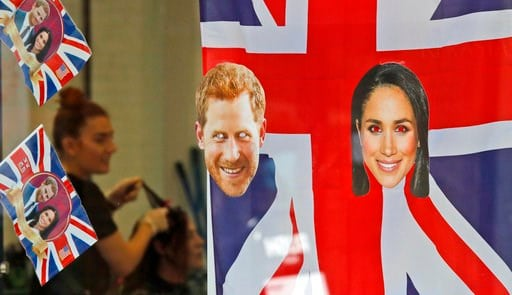 (AP Photo/Frank Augstein). A woman gets a haircut as the shop window is decorated with flags and pictures of Britain's Prince Harry and Meghan Markle in Windsor, Tuesday, May 15, 2018.