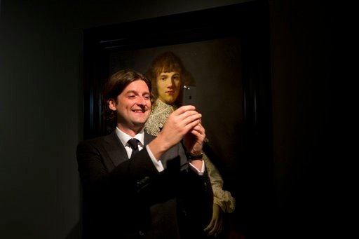 (AP Photo/Peter Dejong). Art dealer Jan Six takes a selfie with a painting attributed to famous Dutch Master Rembrandt after it was put on display at the Hermitage museum in Amsterdam, Netherlands, Wednesday, May 16, 2018. The unsigned painting which w...