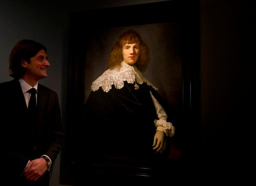 (AP Photo/Peter Dejong). Jan Six poses with a painting attributed to famous Dutch Master Rembrandt after it was put on display at the Hermitage museum in Amsterdam, Netherlands, Wednesday, May 16, 2018. The unsigned painting which will be sold by galle...