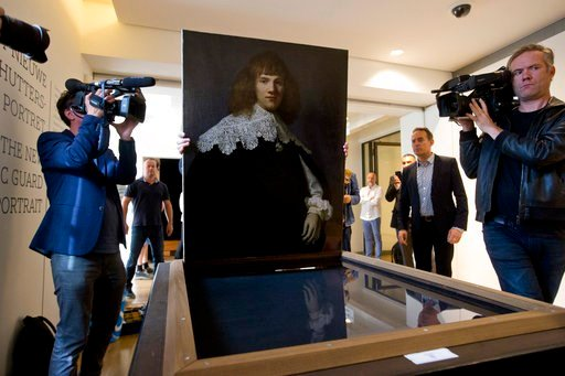 (AP Photo/Peter Dejong). A painting attributed to famous Dutch Master Rembrandt is prepared for display at the Hermitage museum in Amsterdam, Netherlands, Wednesday, May 16, 2018. The unsigned painting which will be sold by gallery owner Jan Six, after...