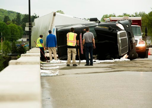 (Larry Deklinski/The News-Item via AP). Emergency personnel look at a Freightliner tractor-trailer, which was overturned by strong winds associated with a thunderstorm, while crossing the Susquehanna River at Danville, Pa., on Tuesday, May 15, 2018. Th...