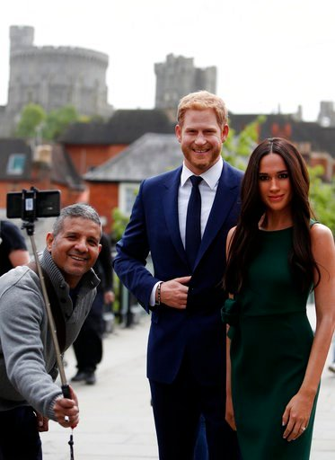 (AP Photo/Alastair Grant). A tourist poses to take a photo of the waxwork figures of Britain's Prince Harry and Meghan Markle against a backdrop of Windsor Castle, in Windsor, England, Wednesday, May 16, 2018. Preparations continue in Windsor ahead of ...