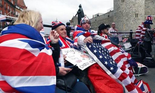 (AP Photo/Alastair Grant). Royal fans John Loughry, right, and Terry Hutt, center, show off their placards as TV and journalists film and interview them in just outside Windsor Castle, in Windsor, England, Wednesday, May 16, 2018. Preparations continue...